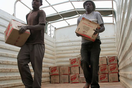 Workers offload boxes of cooking oil for the food distribution in Kibauni, Kenya. Photo: George Arende