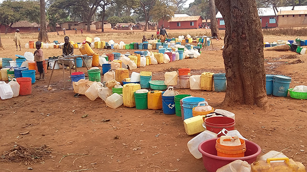 Near a dry water tap connected to an empty water tank, colorful buckets left in a queue wind like thirsty snakes, waiting patiently. Photo: Aaron Tate / CWS
