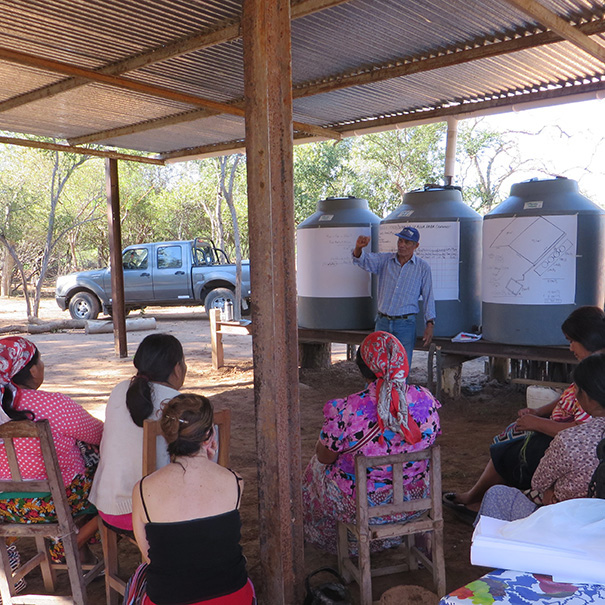 Anacleto Montes presents his family's cistern and water catchment system to a group of visiting Wichi indigenous women. Photo: Margot DeGreef / CWS