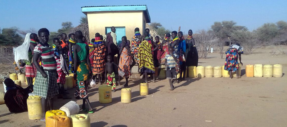 Women and children waiting in line for water in Kenya.